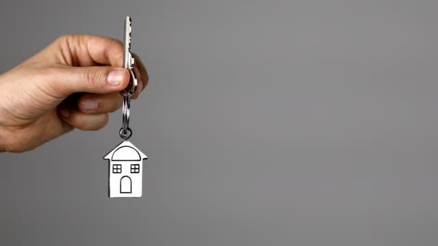 woman holding keys of a new home on a house shaped key ring - house key stock videos & royalty-free footage