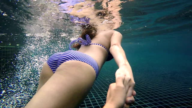 Woman holding man's hand and leading him under the water in swimming pool
