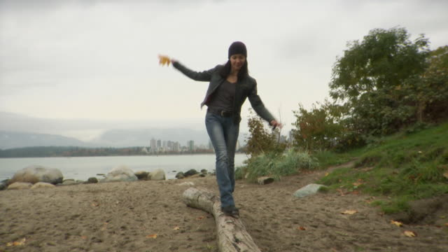 WS TD TU Woman holding maple leaf walking on log on Kitsilano beach / Vancouver, British Columbia, Canada
