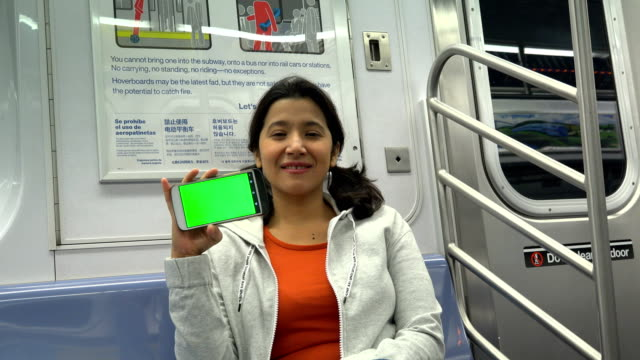 vidéos et rushes de woman holding mobile phone, green screen, subway station, new york city - panneau