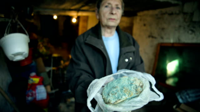 Woman holding moldy loaf of bread