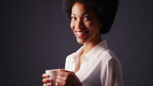 woman holding mug of hot tea and smiling