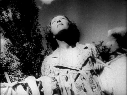 B/W 1927 woman holding onto clothesline + looking up outdoors / newsreel