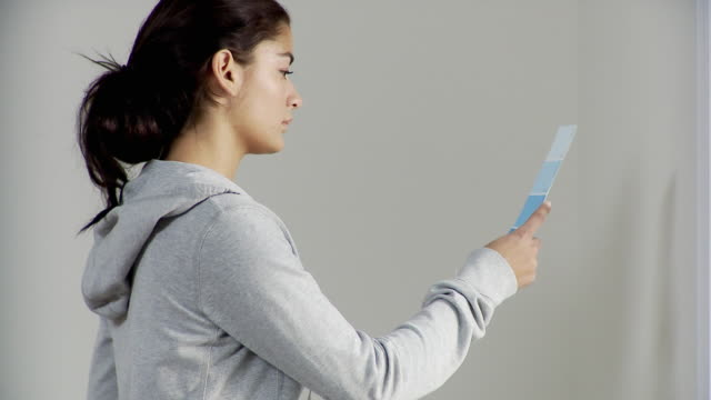 CU, Woman holding paint swatches in front of white wall, Plainfield, New Jersey, USA