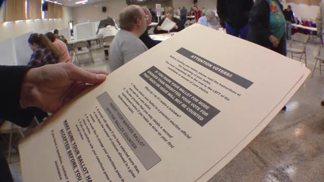 vídeos de stock, filmes e b-roll de cu, woman holding paper folder with voting ballot at polling place, st, marys, ohio, usa - título de eleitor