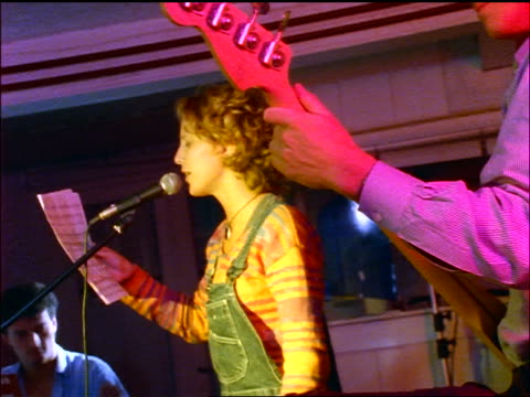 canted woman holding paper singing into microphone / man's hand playing bass in foreground / keyboard in background - rock group stock videos and b-roll footage