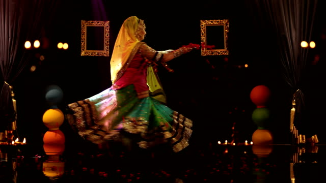 ms woman holding plate of rose petals while performing traditional ghoomar dance on stage/ india - カーテン止め点の映像素材/bロール