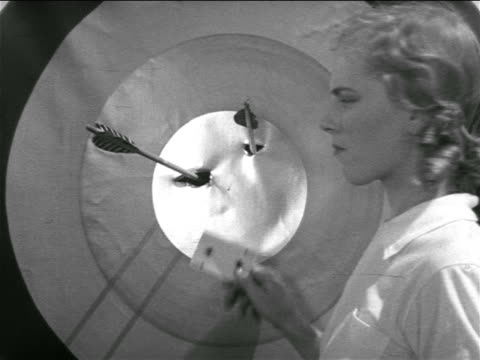 b/w 1938 woman holding playing card up to bullseye on target - bull's eye stock videos and b-roll footage