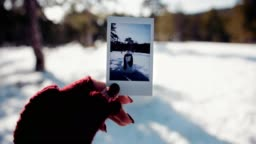 Woman holding polaroid photo of snowman in snowy mountain forest