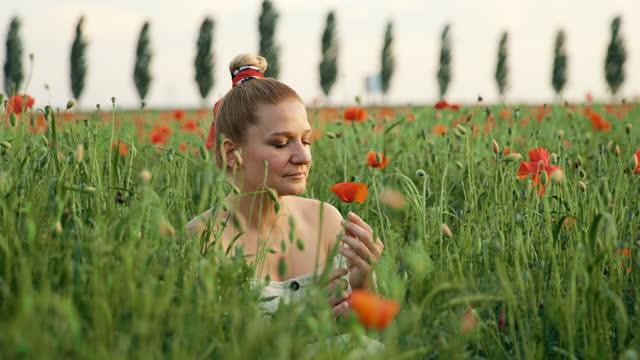 slow motion donna che tiene il fiore di papavero in mezzo al campo - vestito bianco video stock e b–roll
