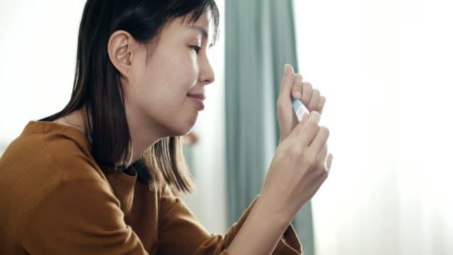 woman holding positive pregnancy test kit - ovulazione video stock e b–roll