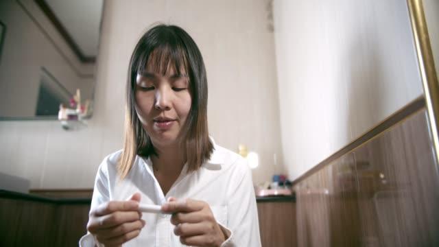 donna in possesso di un kit di test di gravidanza positivo - ovulazione video stock e b–roll