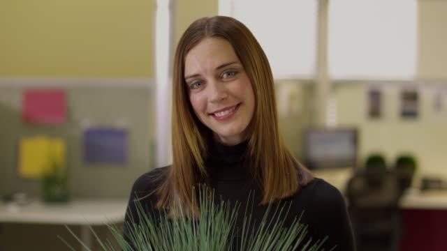 cu woman holding potted plant in office, appleton, wisconsin, usa - ウィスコンシン州アップルトン点の映像素材/bロール