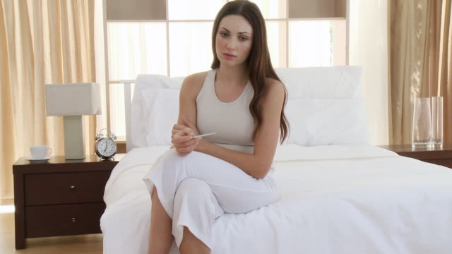 MS Woman holding pregnancy test, sitting on bed / Cape Town, Western Cape, South Africa