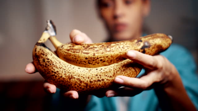 Woman holding rotten banana