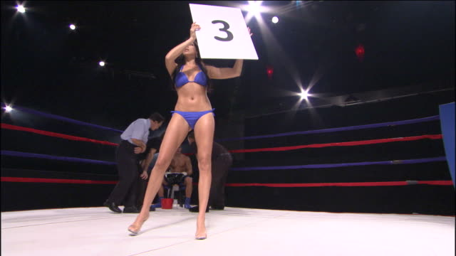 LA WS ZI Woman holding Round 3 sign in boxing ring while trainers and referee assist boxer in corner / Jacksonville, Florida, USA