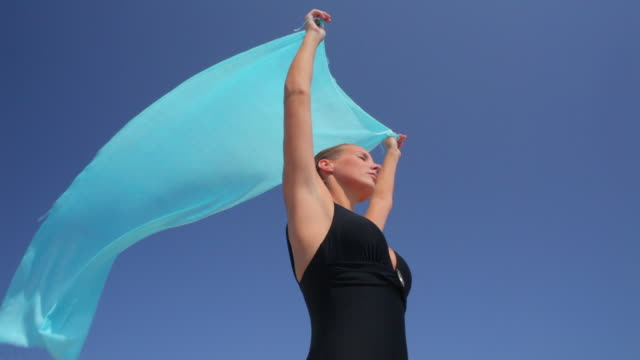 LA Woman holding sarong in the breeze,blue sky,Mallorca