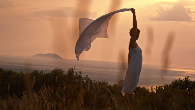 SLO MO Woman holding shawl in the wind