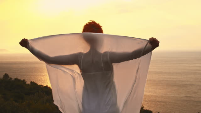 slo mo woman holding shawl in wind on a coast - shawl stock videos and b-roll footage