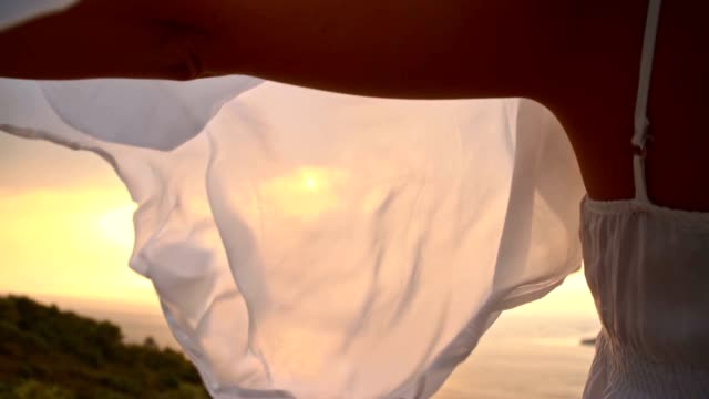 SLO MO Woman holding shawl in wind on a coast