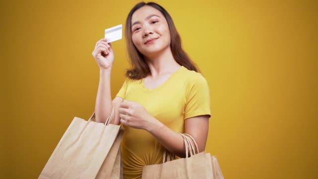 Femme retenant des sacs de magasinage et carte de crédit sur le fond jaune isolé