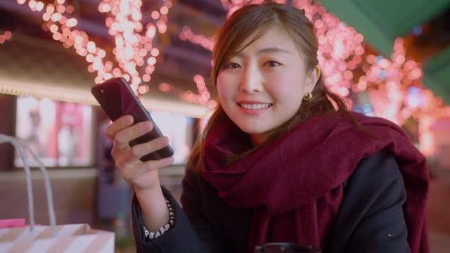 vidéos et rushes de femme retenant des sacs à provisions et utilisant le téléphone intelligent dans la ville la nuit - manteau et blouson d'hiver