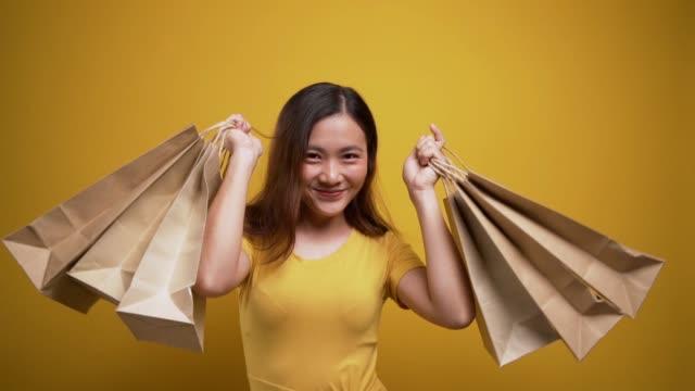 Femme retenant des sacs de magasinage sur le fond jaune isolé