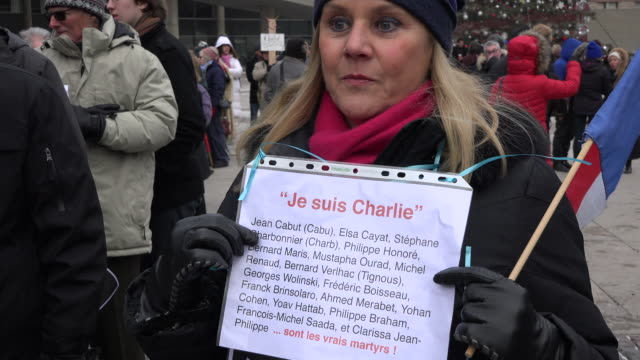 woman holding sign while people sign condolences book in nathan phillips square. hundreds of people protested terrorism and supported france by... - signierstunde stock-videos und b-roll-filmmaterial