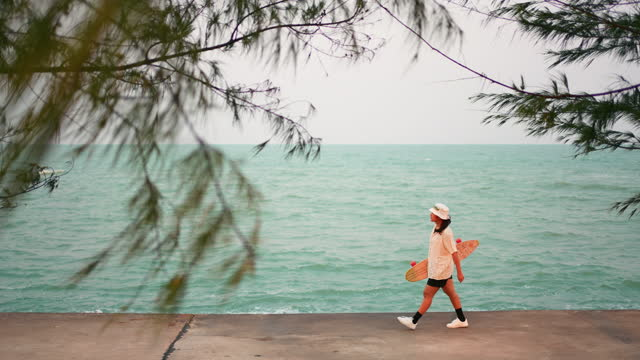 woman holding skateboard in hand walking near the sea - wide stock videos & royalty-free footage
