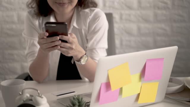 vídeos de stock e filmes b-roll de woman holding smart phone and using laptop computer - caderno de notas