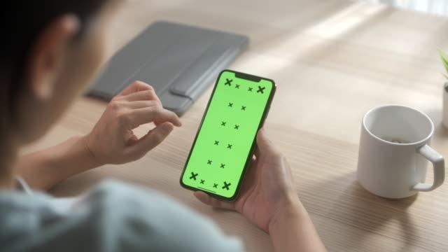 stockvideo's en b-roll-footage met vrouw die slimme telefoon met groen scherm houdt - duwen