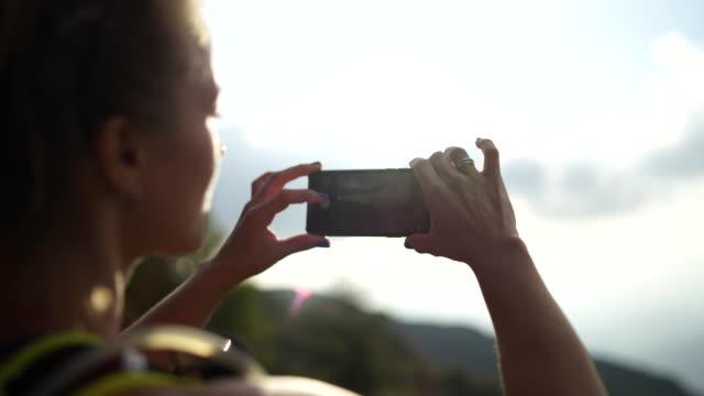 frau mit smartphone nimmt bild sonnenuntergang - einzelne frau über 30 stock-videos und b-roll-filmmaterial
