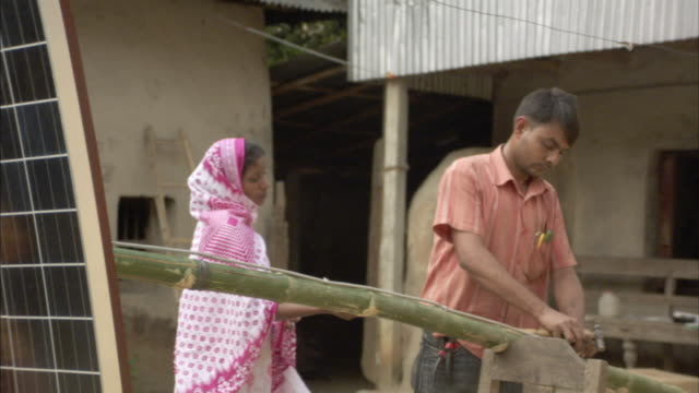ms, zo, woman holding solar panel while man is hammering cord  to bamboo pole, mawna, bangladesh - bangladesh stock videos & royalty-free footage