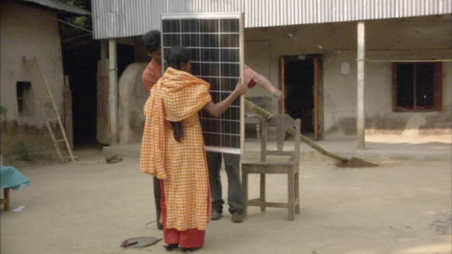 MS, ZI, Woman holding solar panel while two men are tying it onto bamboo pole, Mawna, Bangladesh