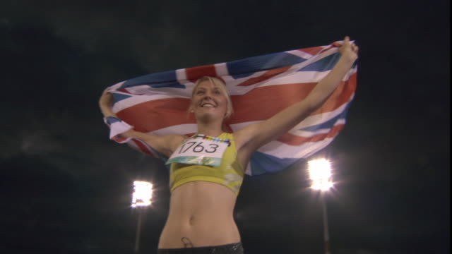 LA MS Woman holding up British flag after winning track and field event/ Sheffield, England