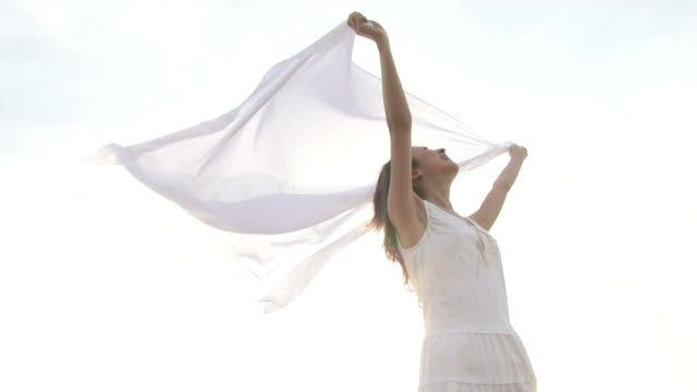 Woman holding white cloth blowing in breeze