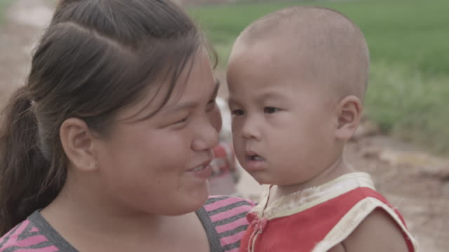 a woman holds a baby boy near a field in china. - two generation family stock videos & royalty-free footage