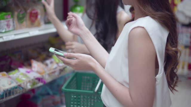 vídeos de stock, filmes e b-roll de mulher é um dispositivo inteligente em branco em loja de departamento. - loja de produtos eletrônicos