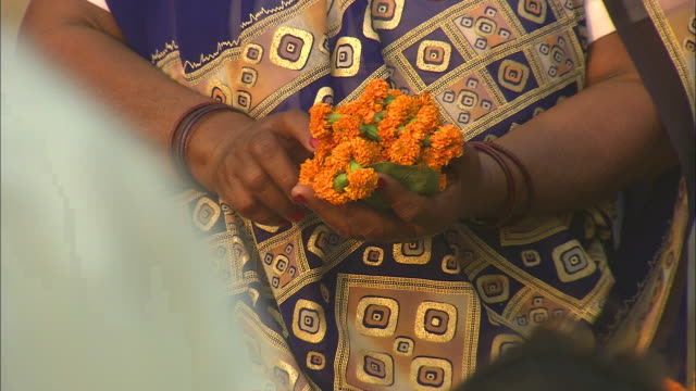a woman holds a bundle of marigolds in her hands. - sarong stock videos & royalty-free footage