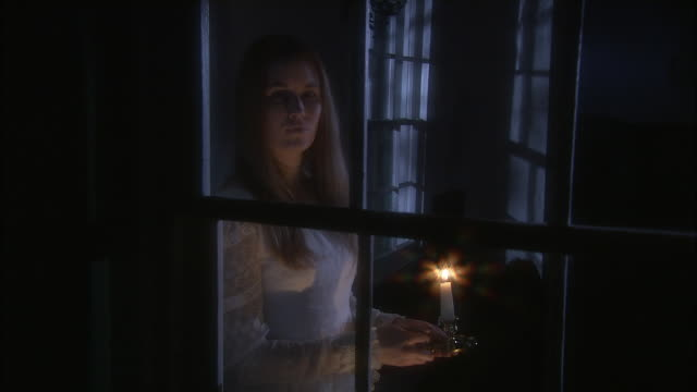 a woman holds a candle and looks out a window. - candle stock videos & royalty-free footage