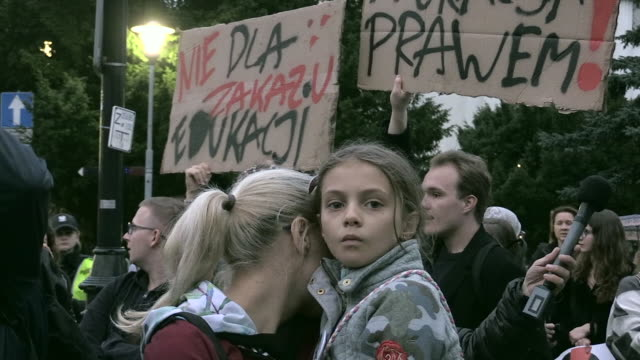 woman holds a child during a demonstration against the criminalization of sex education in warsaw, poland on october 16, 2019. - 性教育点の映像素材/bロール