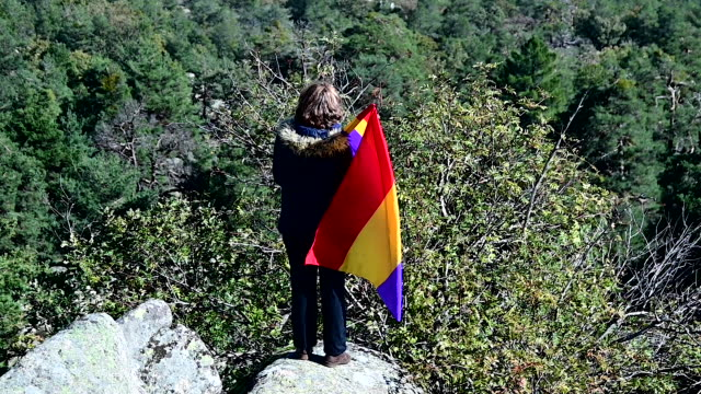 stockvideo's en b-roll-footage met woman holds a flag of the second spanish republic in front of the valle de los caidos mausoleum in san lorenzo del escorial during the exhumation of... - pardo