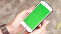 Woman holds a green scren smart phone