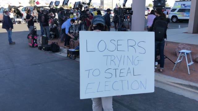 "woman holds a ""losers trying to steal election"" sign outside the clark county election department, where ballots from the election are being counted,... - clark county nevada stock videos & royalty-free footage"