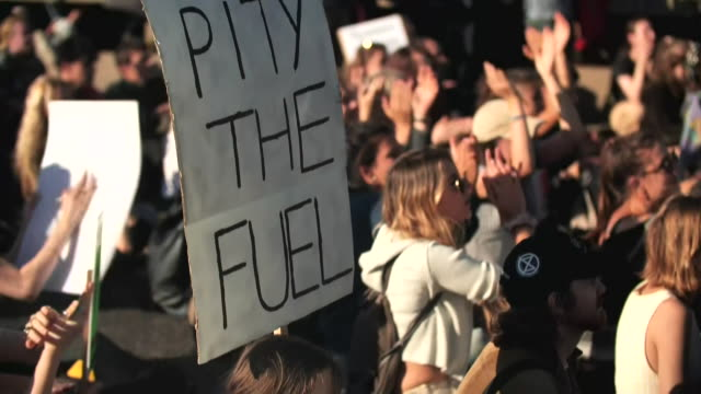 "woman holds a sign that reads ""pity the fuel"" during a climate change protest in london. - environment or natural disaster or climate change or earthquake or hurricane or extreme weather or oil spill or volcano or tornado or flooding stock videos & royalty-free footage"