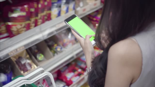 stockvideo's en b-roll-footage met vrouw houdt een slimme telefoon met green screen in warenhuis. - mar