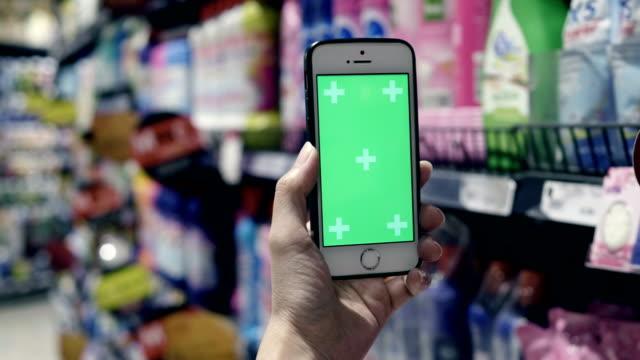 vídeos de stock, filmes e b-roll de mulher mantém um telefone inteligente com tela verde - mercado espaço de venda no varejo