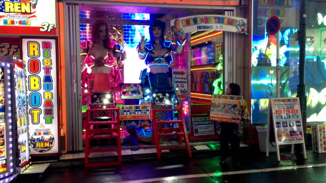 A woman holds an advertising board as she hawks for customers outside the Robot Restaurant in Shinjuku on September 06 2017 in Tokyo Japan