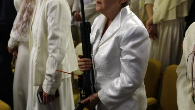 a woman holds an ar15 rifle during a ceremony at the world peace and unification sanctuary in newfoundland pennsylvania on february 28 2018 in... - gewehr stock-videos und b-roll-filmmaterial