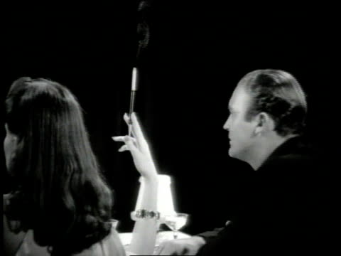 1942 ms woman holds cigarette holder straight up in the air during dinner at restaurant - smoking activity stock videos and b-roll footage